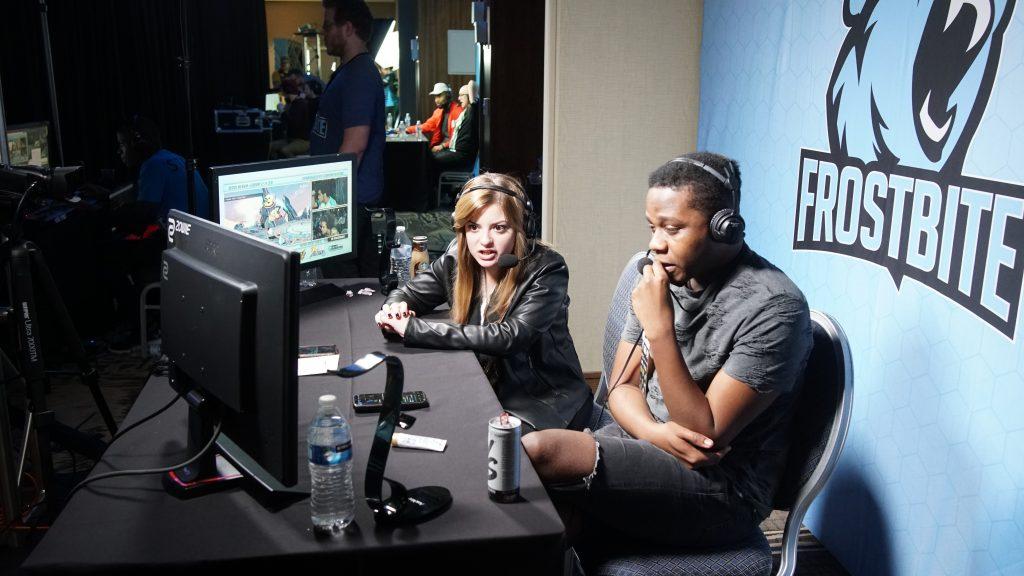 Kaksi nuorta istuu tietokoneen äärellä pelitapahtumassa