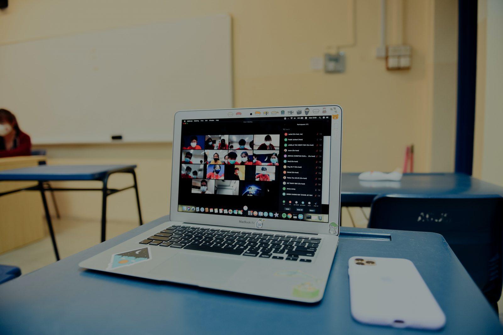 Pöydällä tietokone auki, jossa verkkopalaveri-auki ja monien osallistujien videokuvia auki.