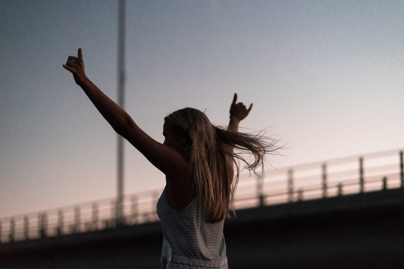 Ihminen pitää käsiä ilmassa jahiukset hulmuaa auringonlaskua vasten.