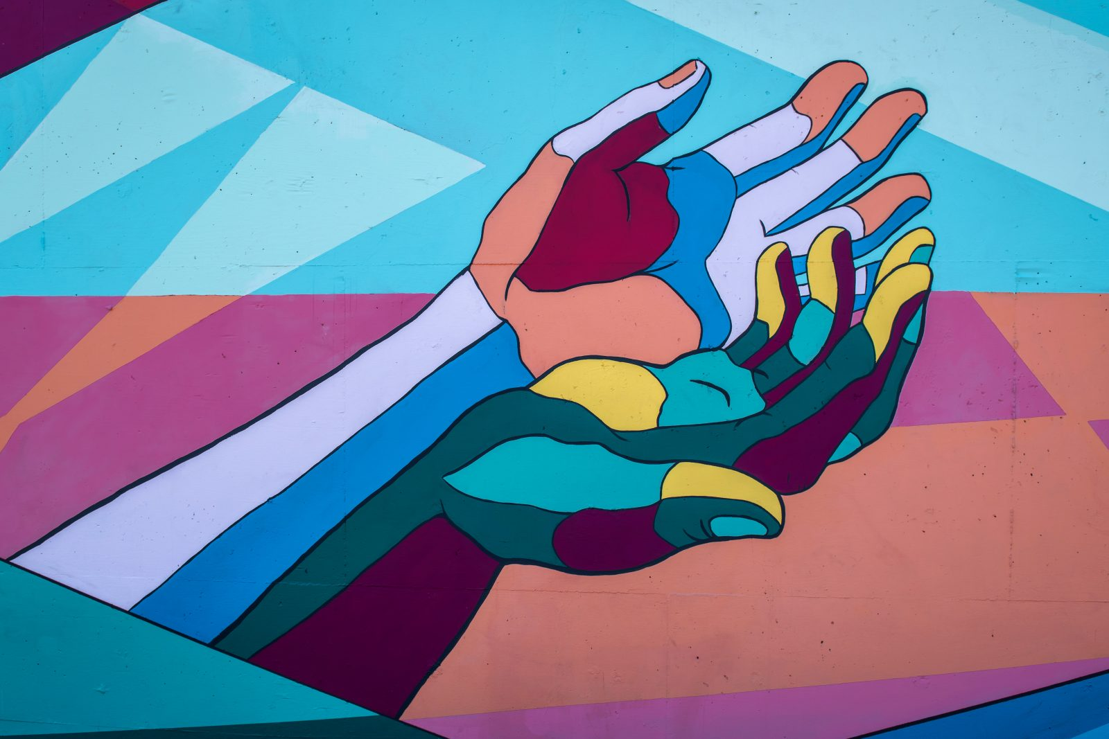Värikäs seinämaalaus, jossa kaksi kättä.
