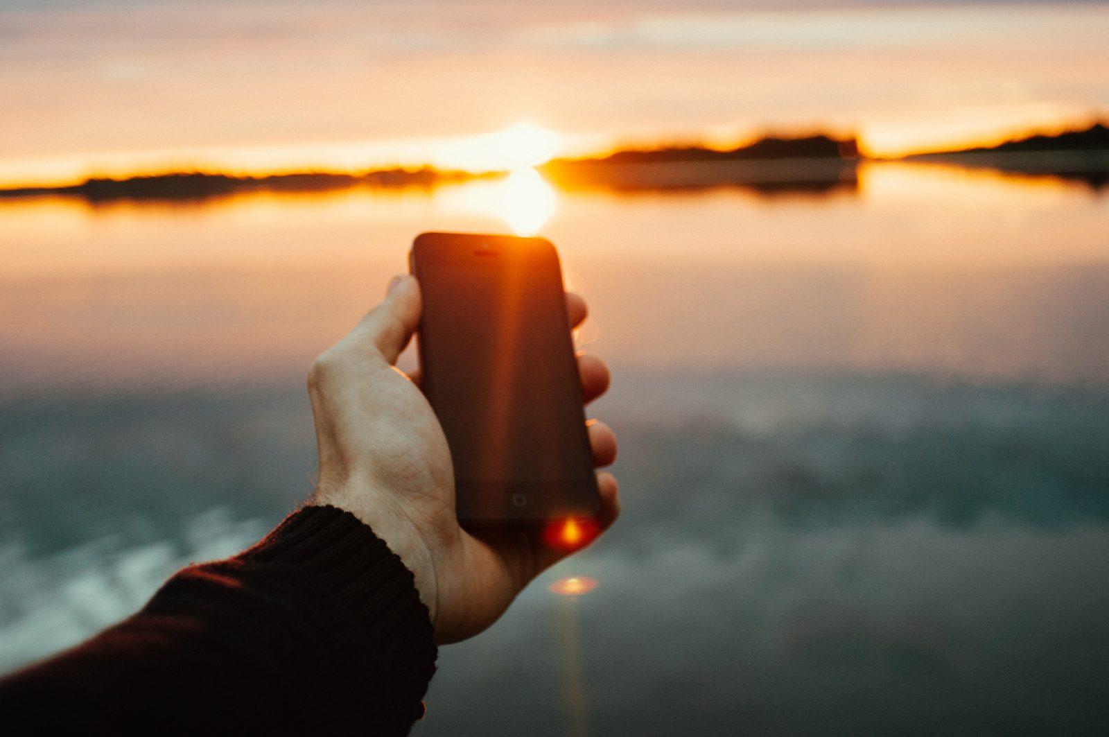 Man med mobiltelefon i handen vid sjön
