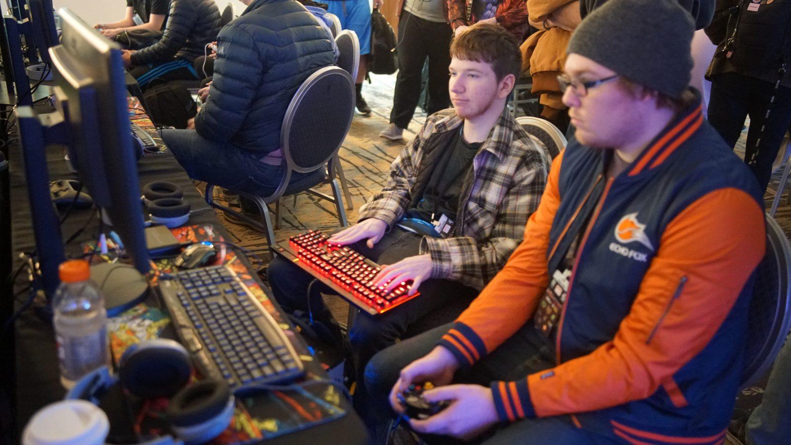 Kaksi henkilöä pelaa tietokoneen edessä vierekkäin.