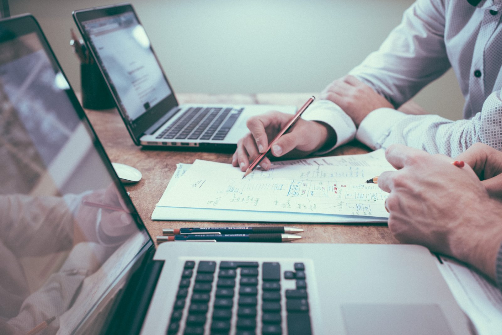 Tietokoneita, joiden välissä pöydällä papereita ja käsi kirjoittaa jotain.