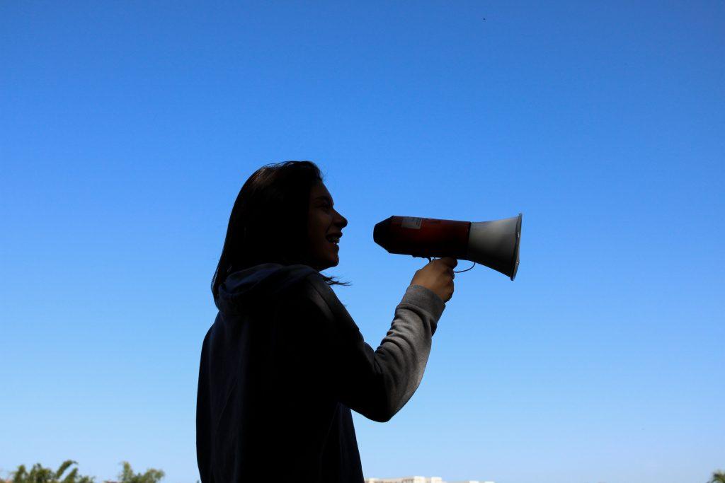 kvinna som skriker till megafon.