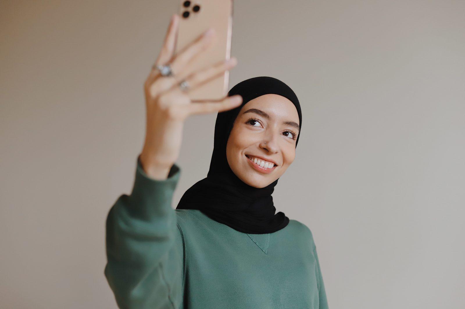 Nainen ottaa itsestään kuvaa hymyillen