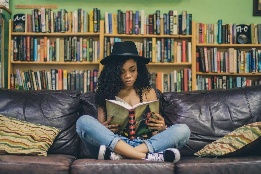 Nainen istuu kirjahyllyn edessä sohvalla ja lukee kirjaa