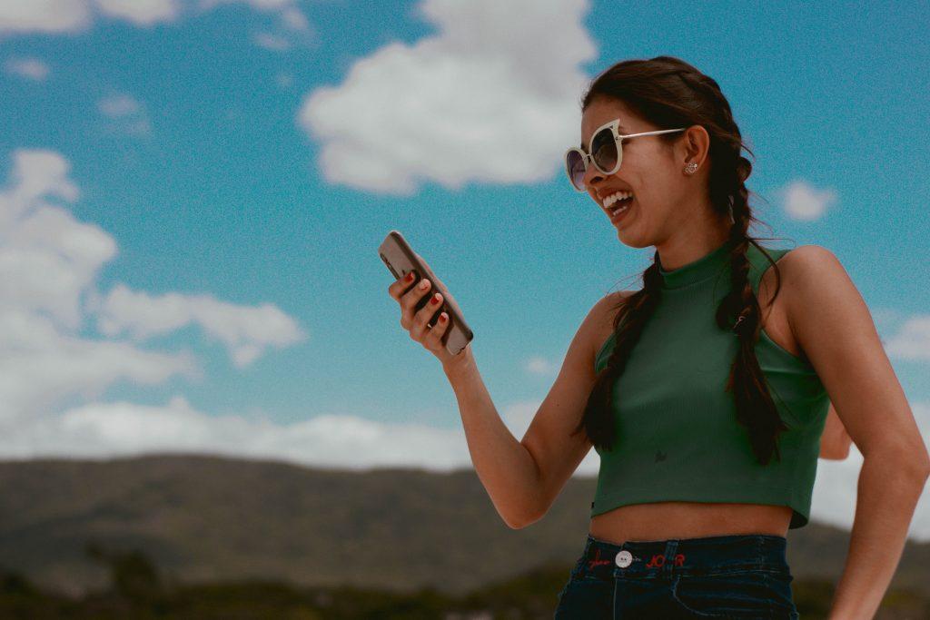 Nainen pitelee iloisena puhelinta kädessä kesällä ulkona.