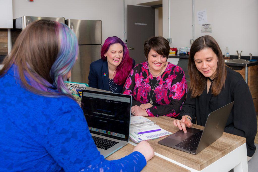Neljä naista istuu pöydän ääressä ja katsoo tietokonetta