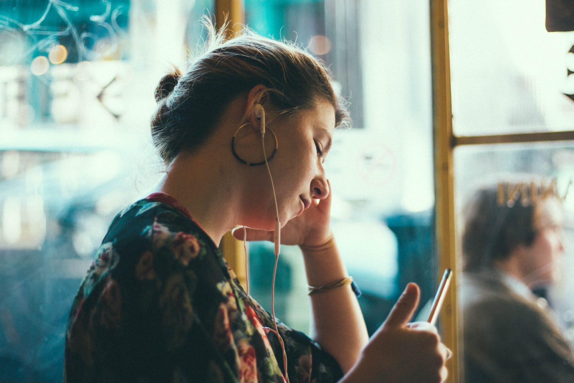 Nainen kuuntelee kuulokkeilla puhelimesta jotain ja katsoo samalla puhelimen ruutua.