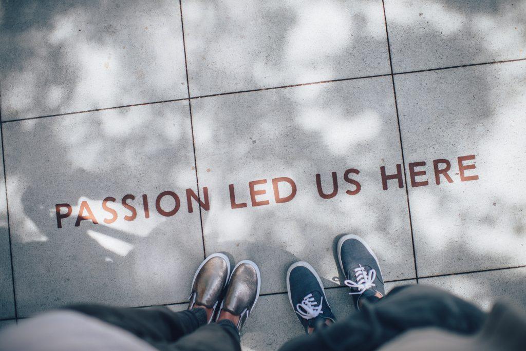 Kaksi ihmistä seisoo massa olevan Passion led us here tekstin ympärillä.
