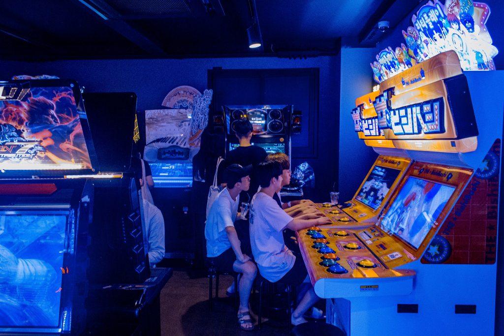 Sinisessä peliluolassa kaksi nuorta pelaamassa koneen äärellä.