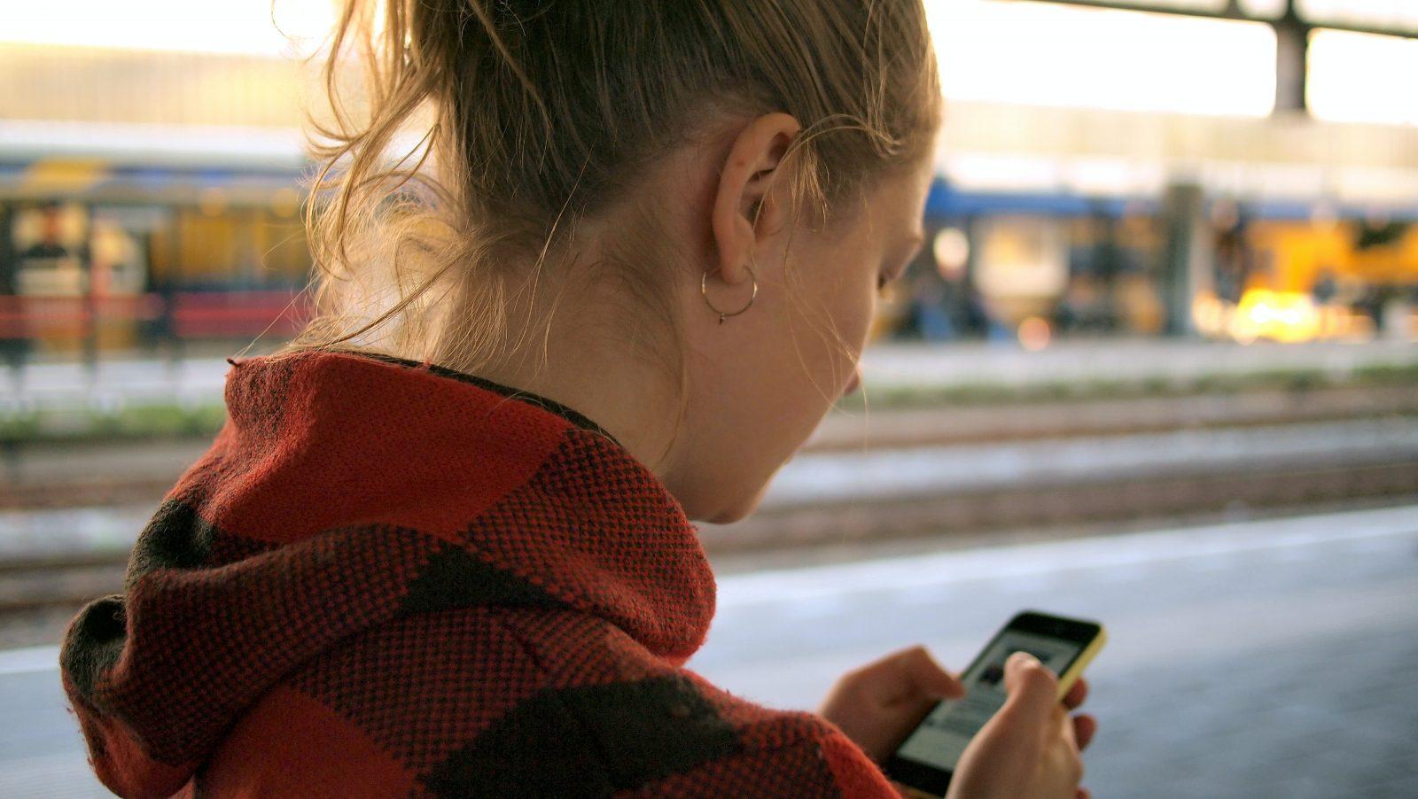 Ihminen pitelee ulkona puhelinta kädessä ja katsoo sen ruutua.