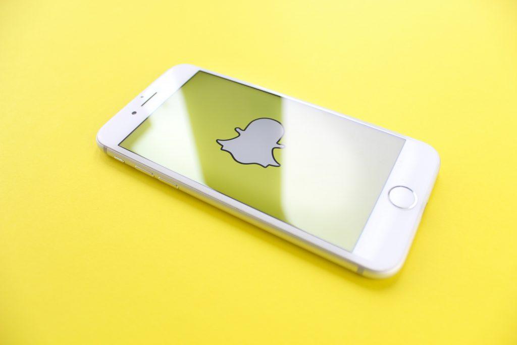 Keltaisella taustalla valkoinen puhelin, jossa on auki Snapchatin logo.