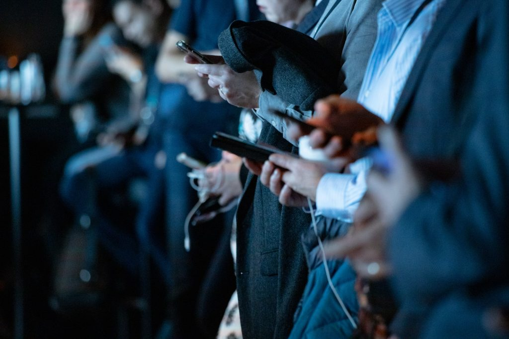människor stor i rad med mobiltelefon i hand