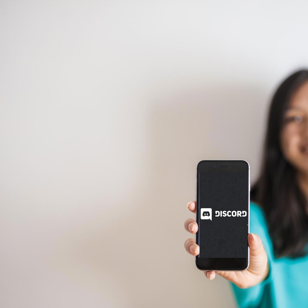 Nainen pitää kameraan kohti puhelinta, jossa on auki Discordin logo tummalla pohjalla.