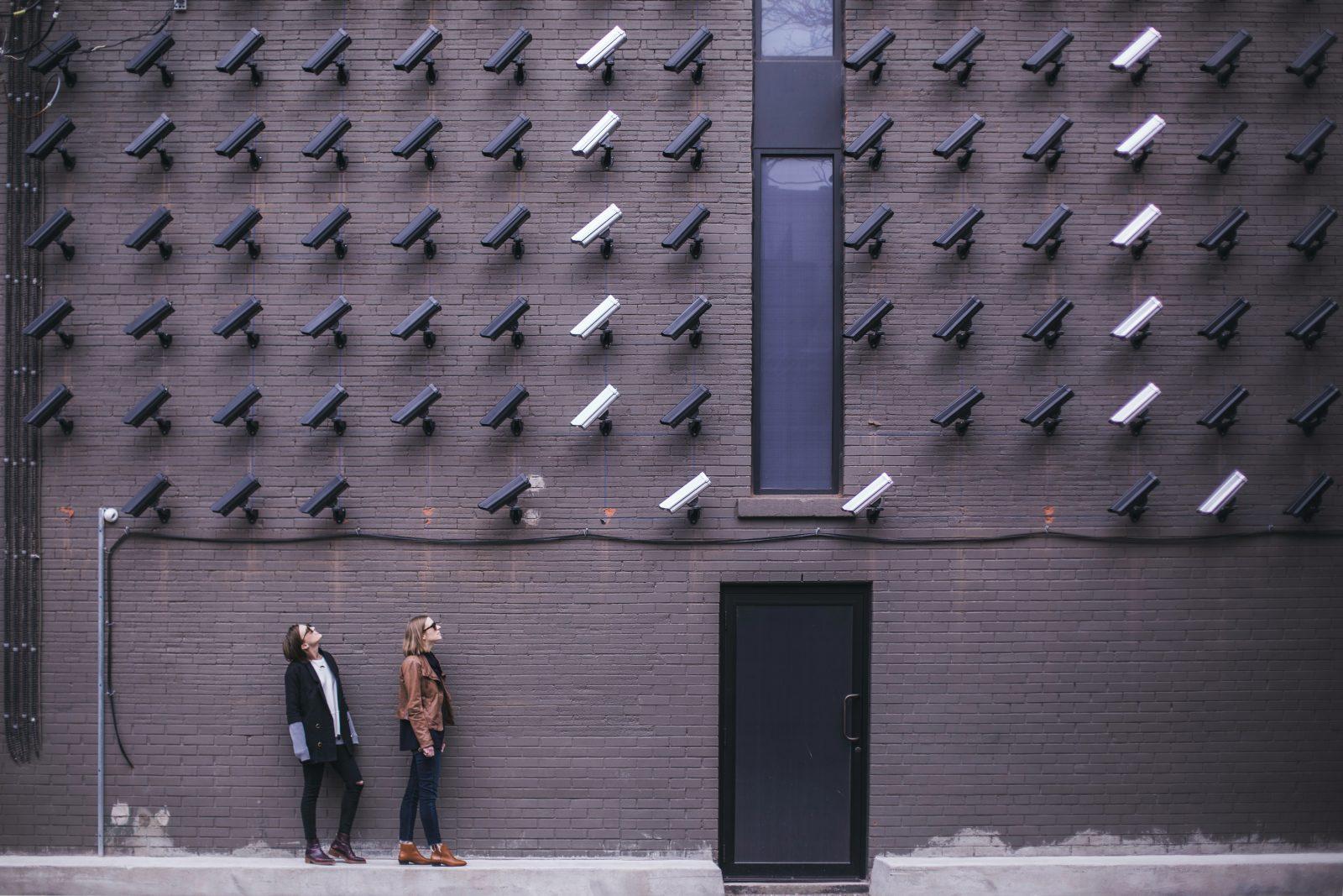 Kaksi ihmistä seisoo talon seinän edessä, missä on koko seinän verran valvontakameroita kohdistettuna heihin.