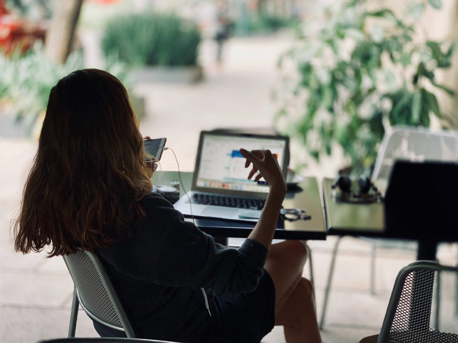 Ihminen istuu ulkona pöydän ääressä tietokoneen edessä varjossa.