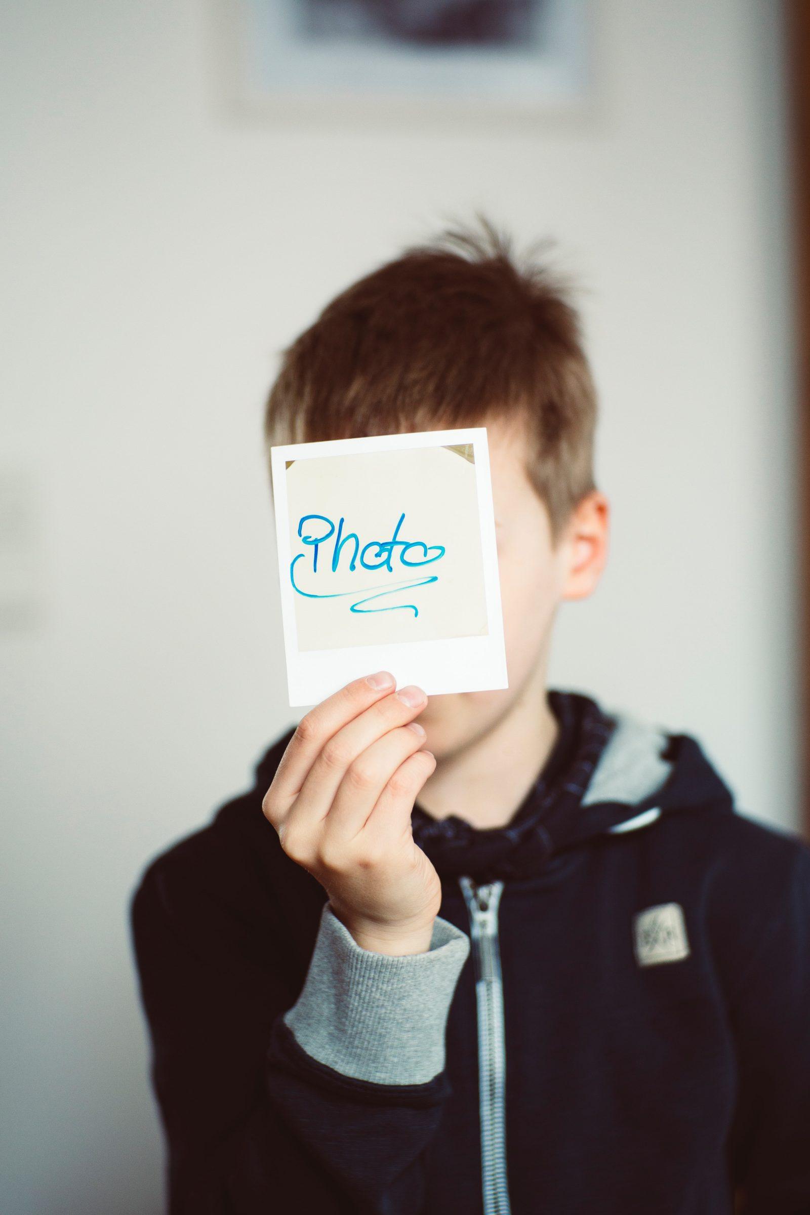 Pieni poika pitää kasvojen edessä polaroid-kuvaa, jossa lukee photo.