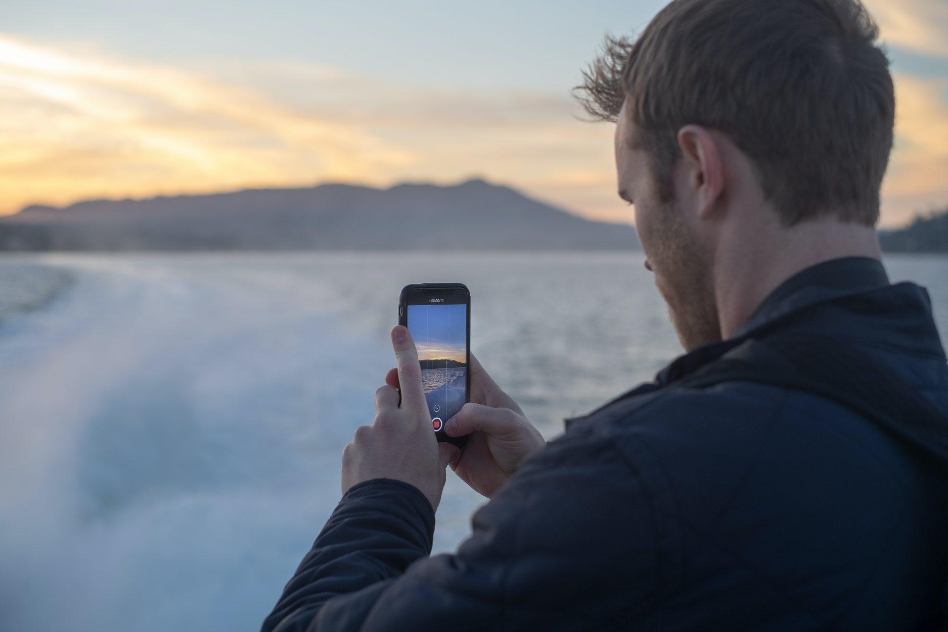 Mies ottaa puhelimella kuvaa ulkona talvimaisemissa selkä kameraan päin.