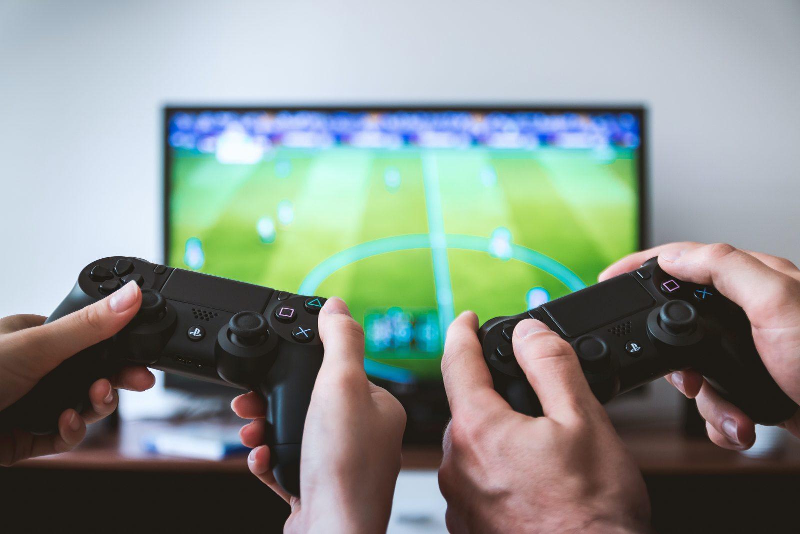 Kahta pelikonsolin ohjainta pidetään käsillä kiinni television edessä.