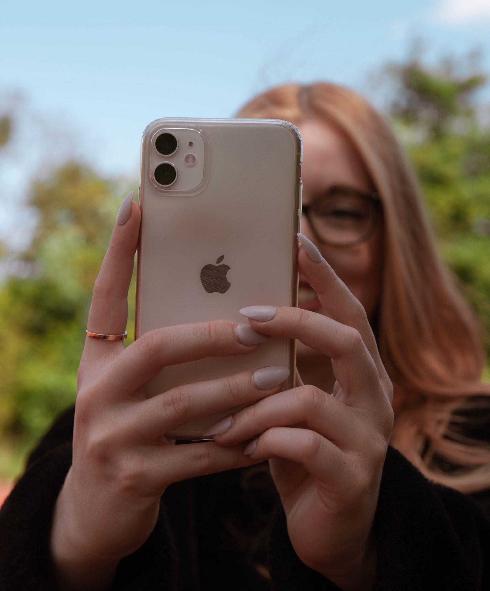 Nainen pitää puhelinta käsissä ulkona.
