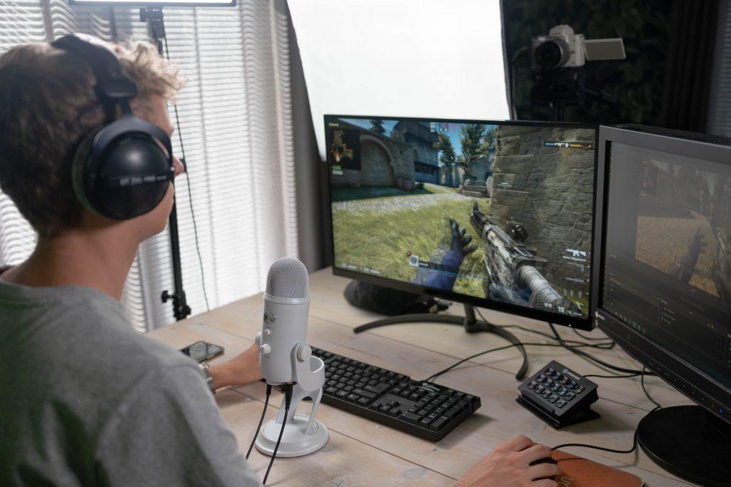 Nuori poika pelaa tietokoneen äärellä tietokonepeliä.