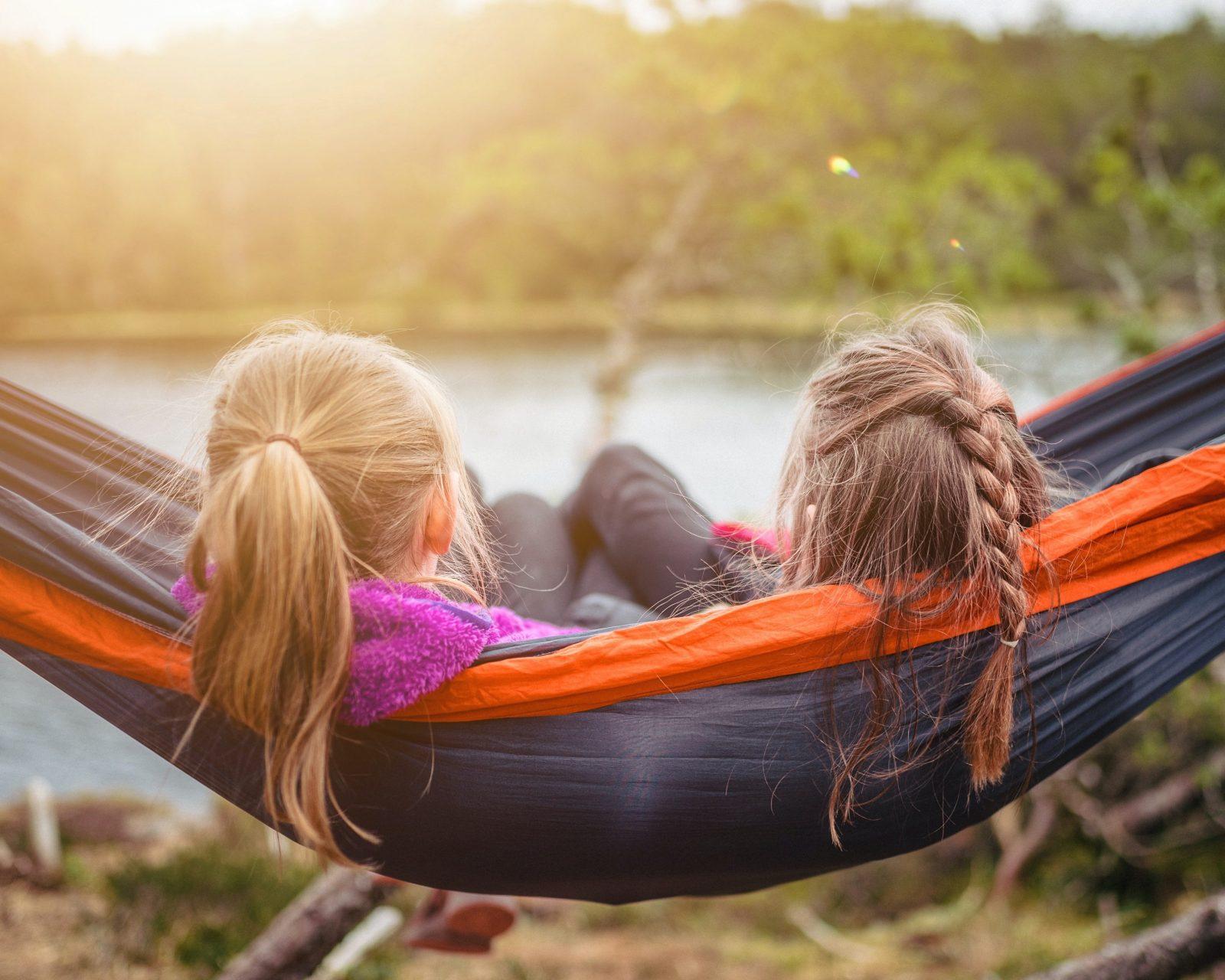 Kaksi henkilö istuu vierekkäin ulkona riippumatossa.