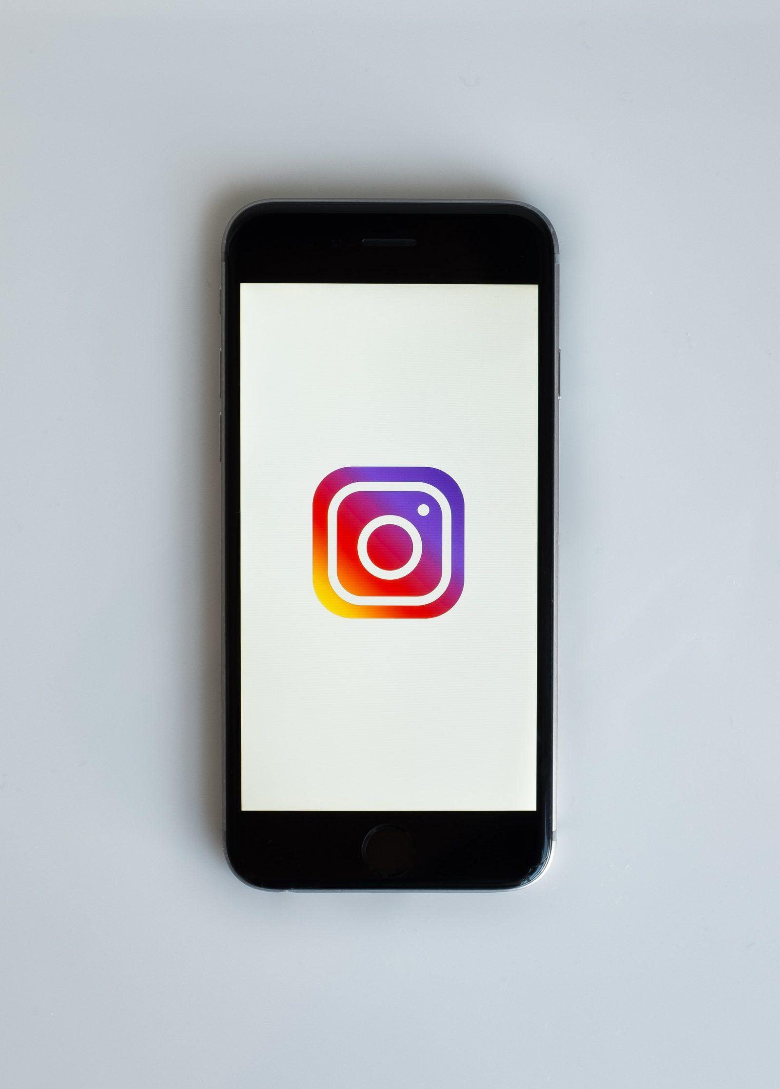Musta puhelin valkoisella taustalla ja auki Instagramin värikäs logo.