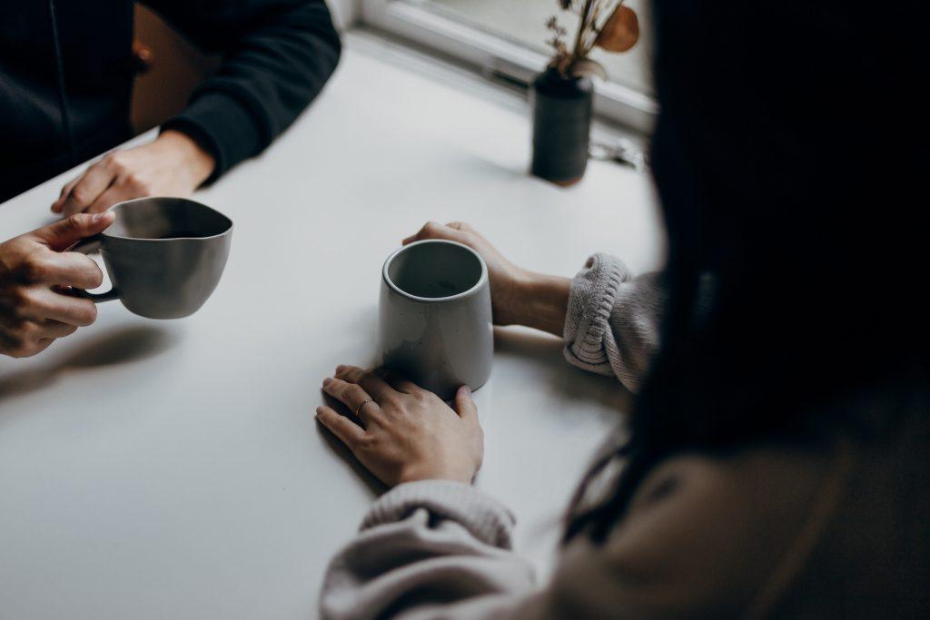 Kaksi ihmistä istuu vastakkain pöydän äärellä kahvikuppien kanssa.