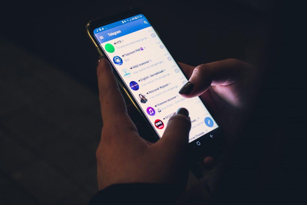 Pimeässä loistaa puhelin, jossa auki Telegram keskustelut.