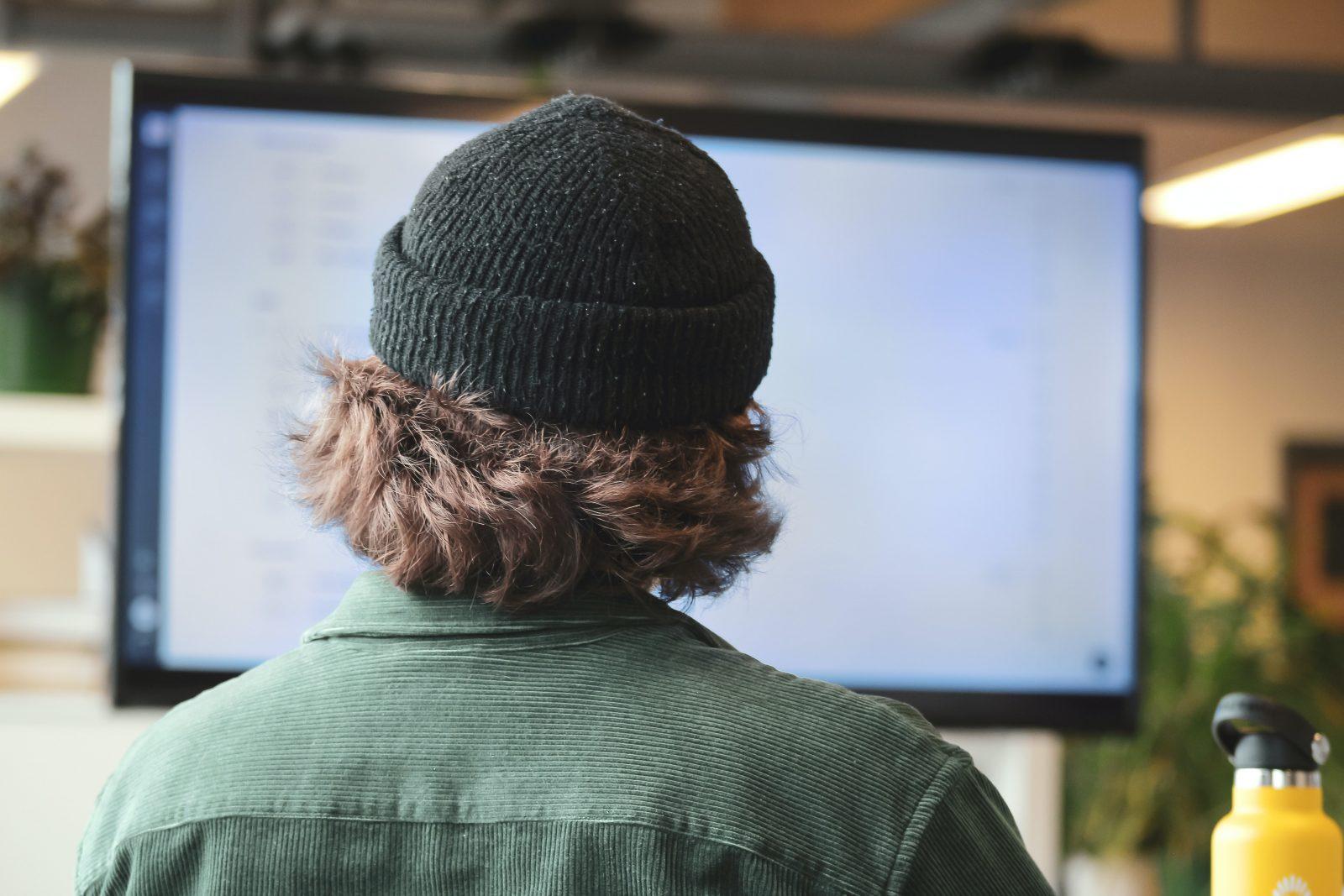 Pipopäinen henkilö istuu tietokoneen ruudun edessä.