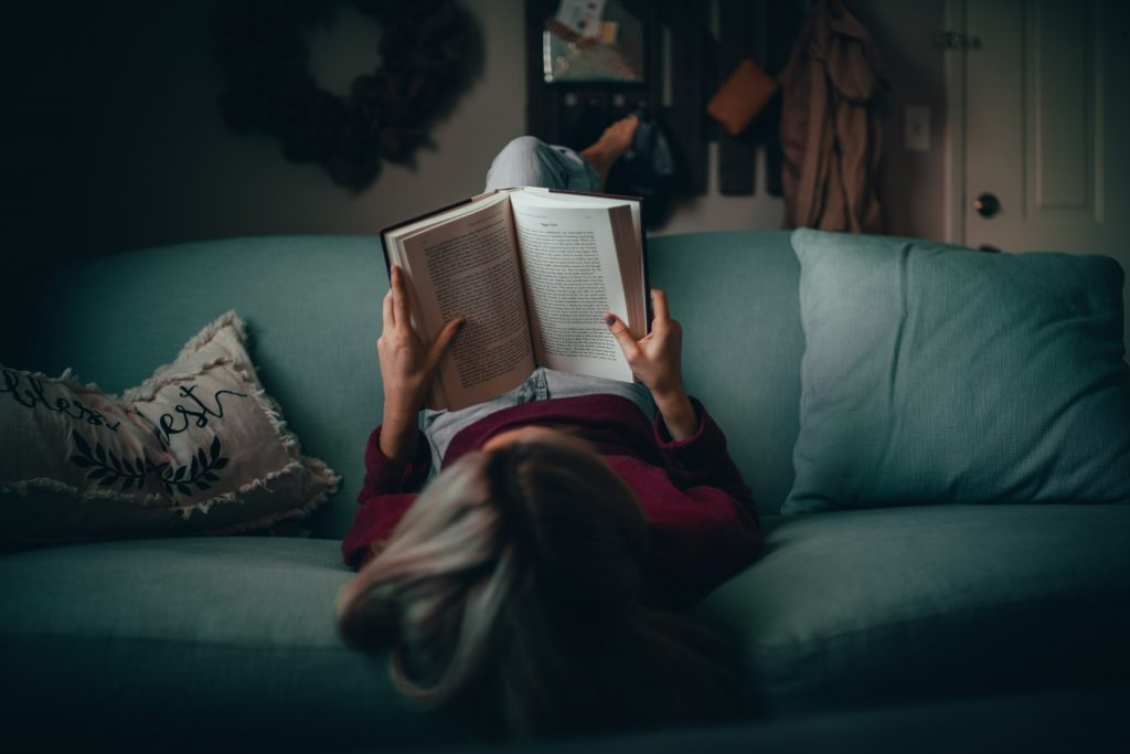 Woman is laying upside down in sofa and reads a book.