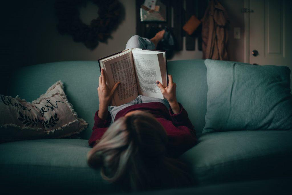 ihminen lukee kirjaa istuen sohvalla väärin päin hiuksien valuessa maata kohti.