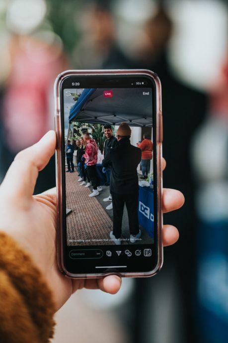 Kädessä pidetään puhelinta ja kuvataan Instagram-liveä ulkotapahtumasta.
