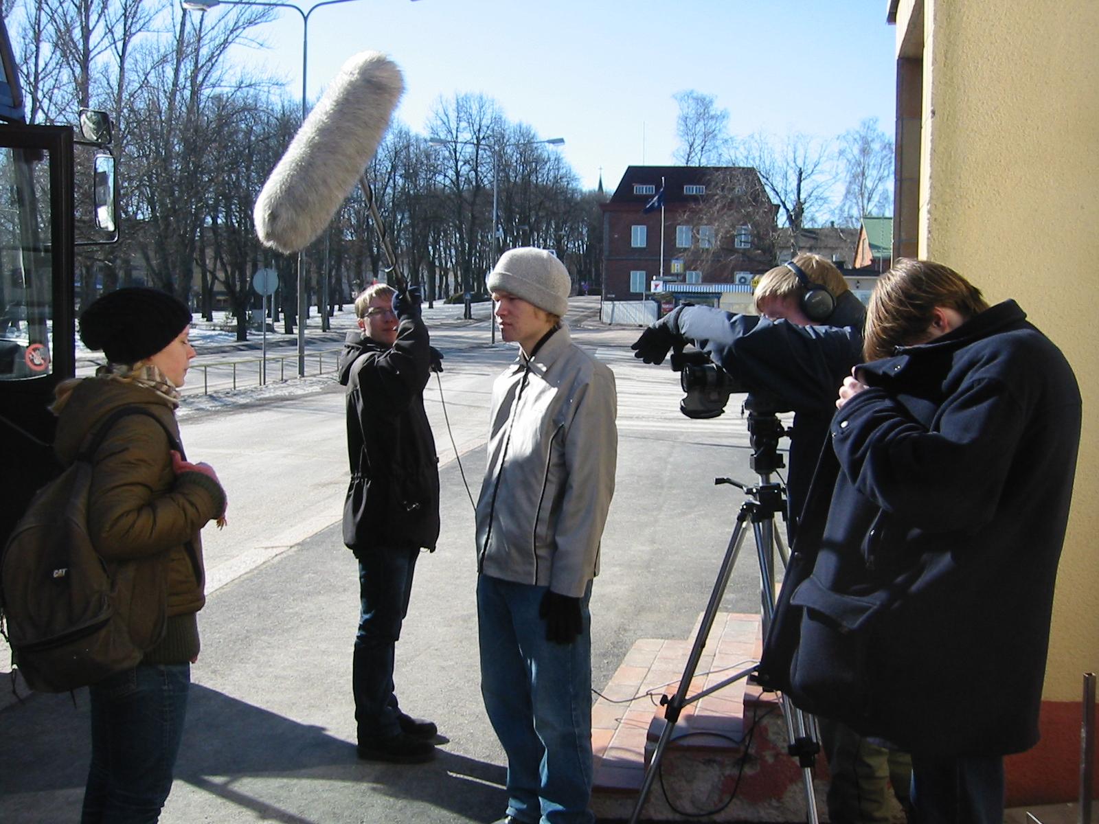 Kadulla kuvataan videota. Yksi henkilö kuvaa videokameralla, yksi pitelee mikkiä ja kaksi henkilöä näyttelee kadulla.