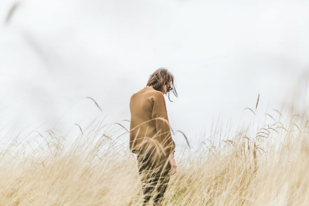 Människa står med ryggen vänt i gräset