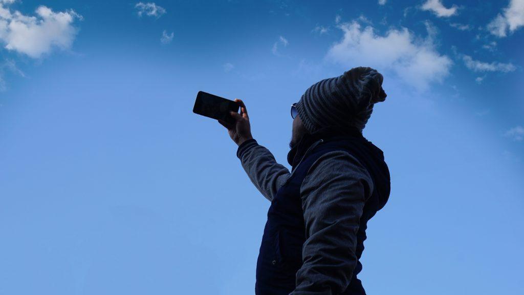 Henkilö ottaa taivasta vasten selfietä talvivaatteissa.