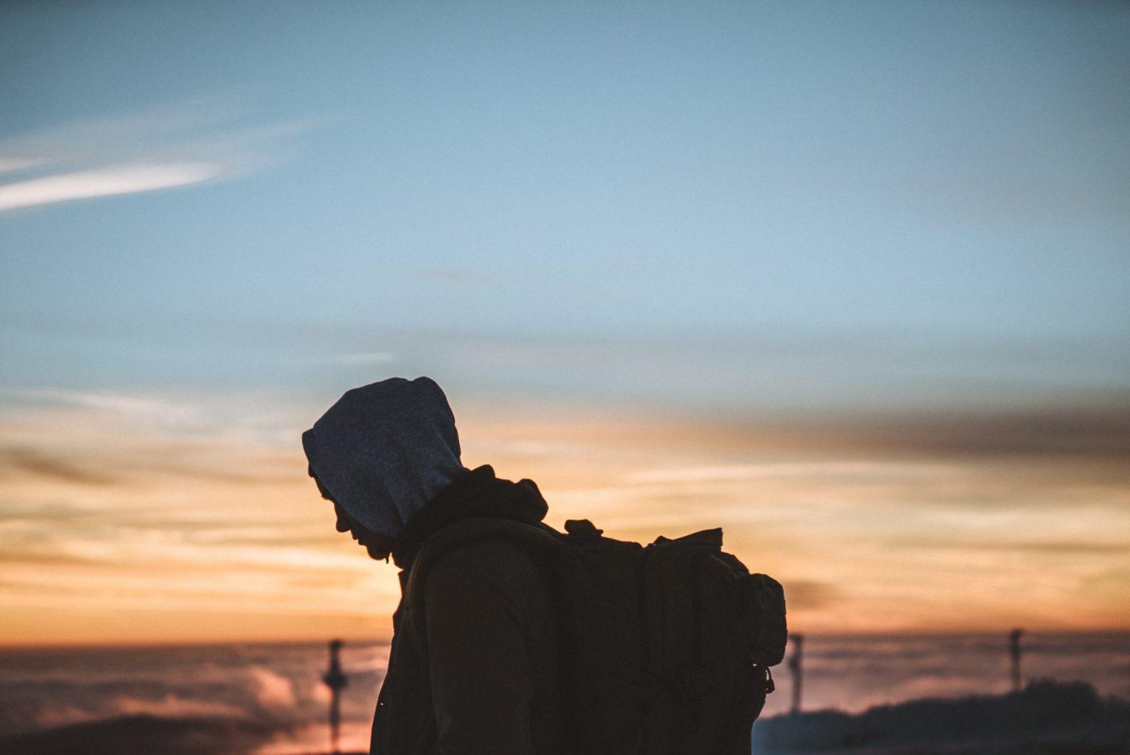 Hahmo katsoo maahan päin huppu päässä auringonlaskun edustalla.