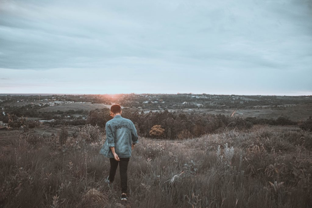 Henkilö kävelee ulkona auringonlaskua kohti.