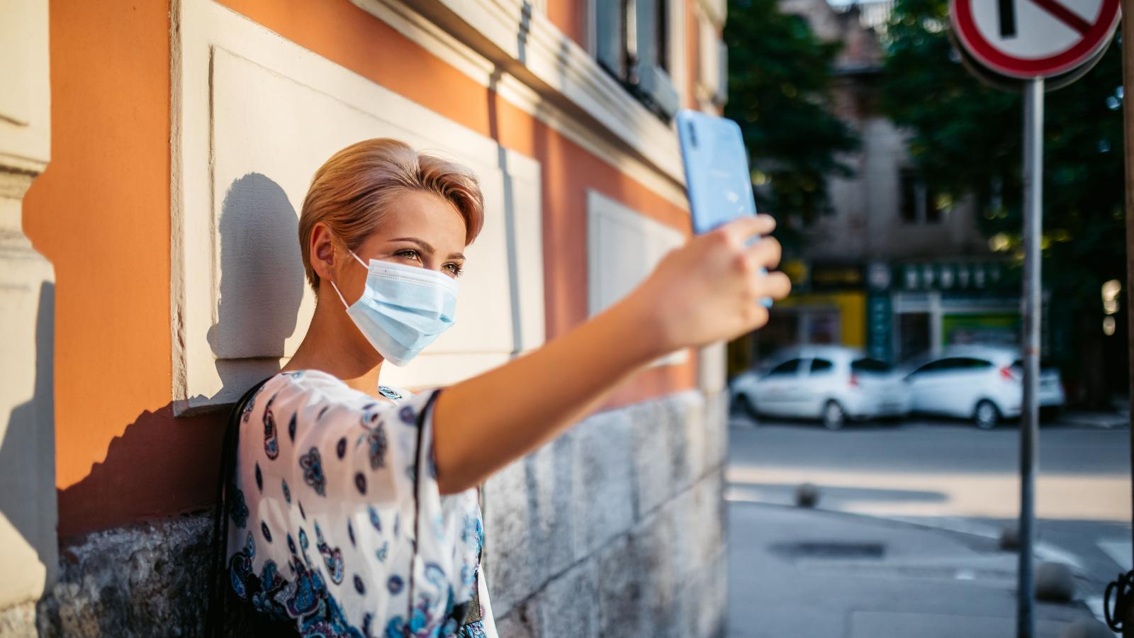 Nainen ottaa puhelimella selfietä seinän edessä kasvomaski naamalla.