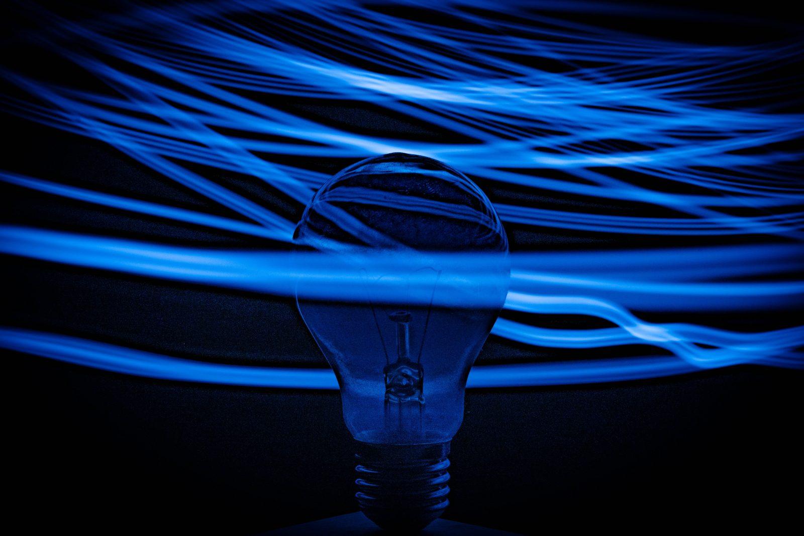 Hehkulamppu sinisessä taustassa josta menee vaaleita säteitä ympäriinsä