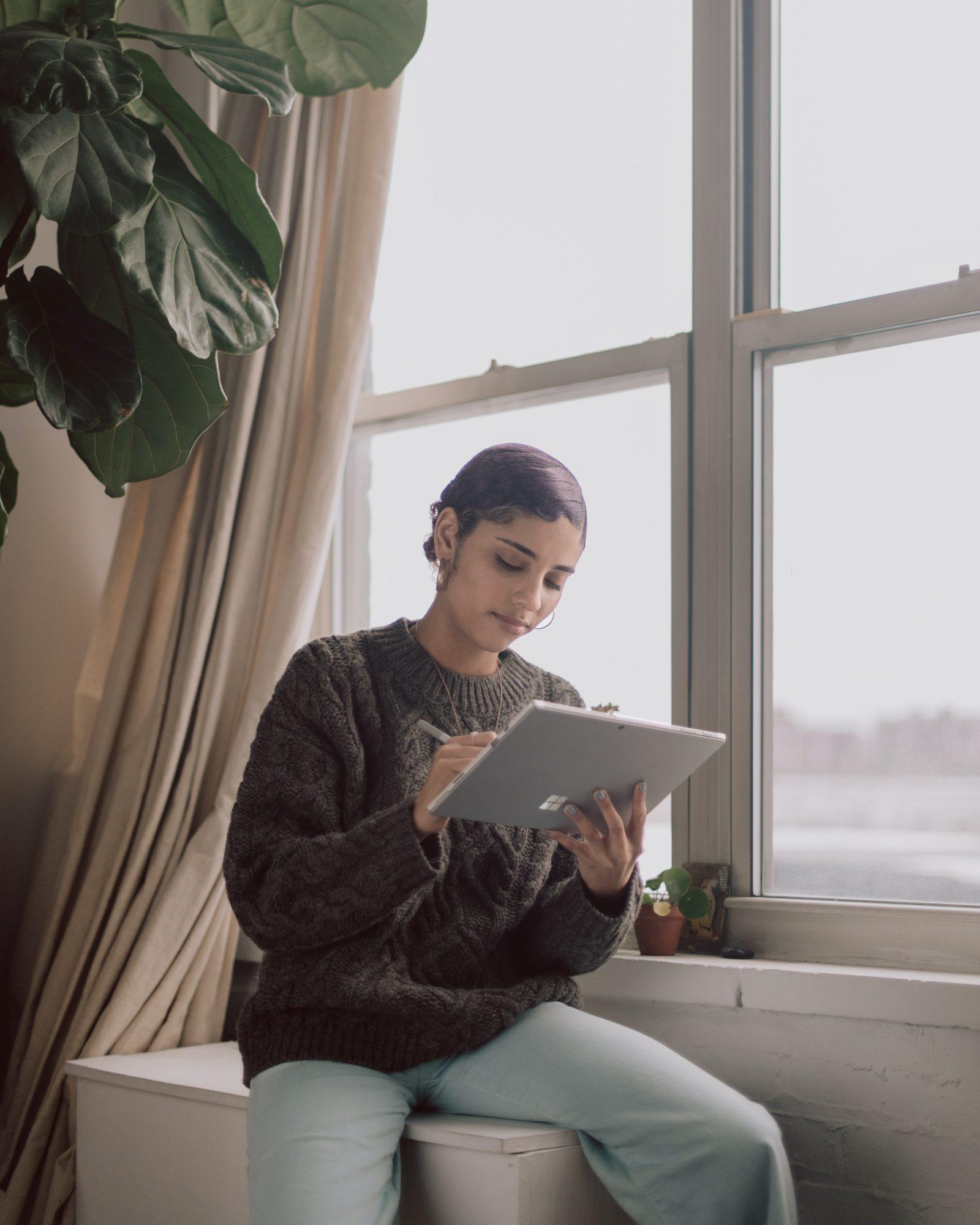 Ihminen istuu ikkunan edessä tabletti kädessä katsoen sen ruutua