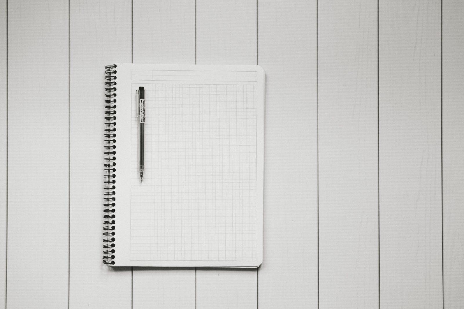 Valkoisella taustalla on tyhjä valkoinen muistio ja sen päällä musta kynä.