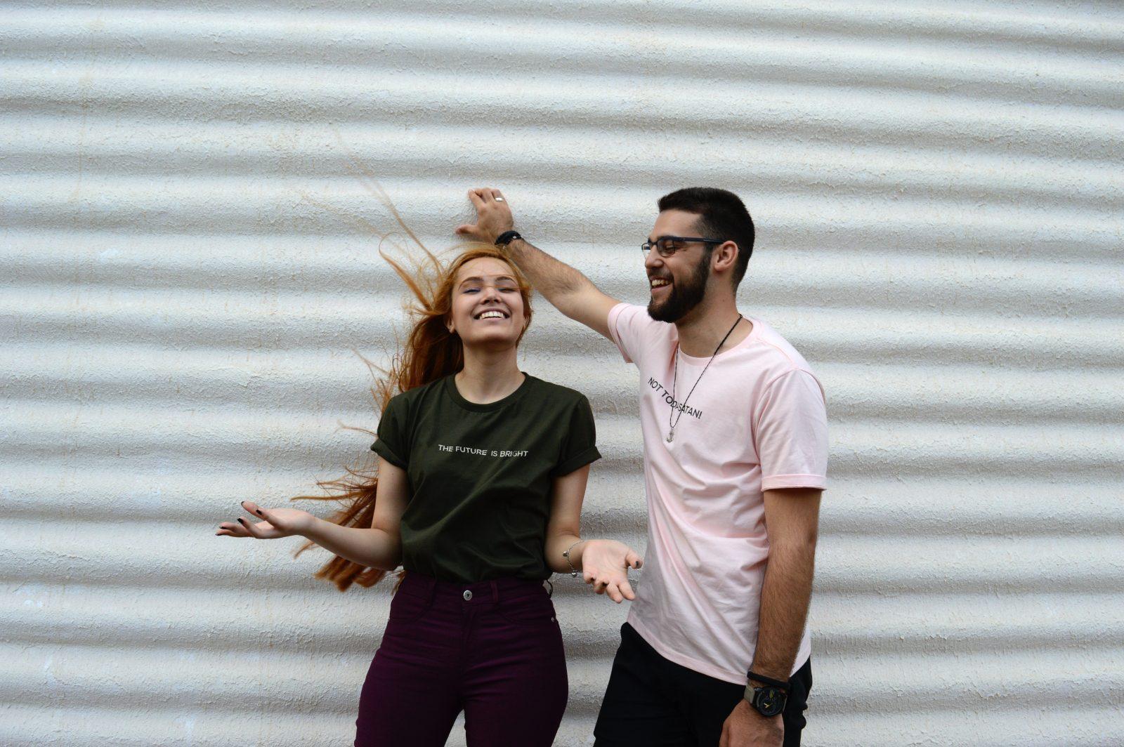 Kaksi nuorta seisoo ulkona harmaan seinän edustalla