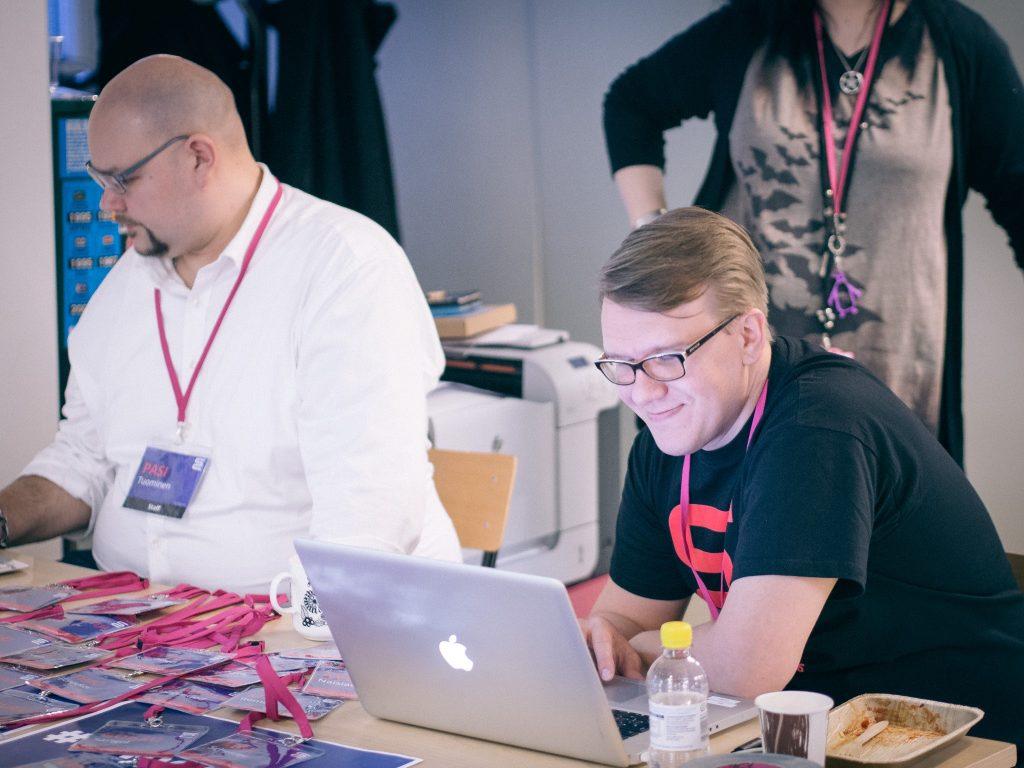 Verken Pasi ja Heikki istuu vierekkäin pöydän ääressä ja katsoo tietokoneita.