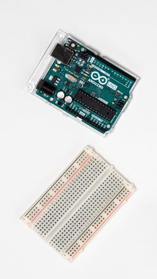 Arduino -kehitysalusta ja kytkentälevy ylhäältäpäin kuvattuna valkoisella taustalla