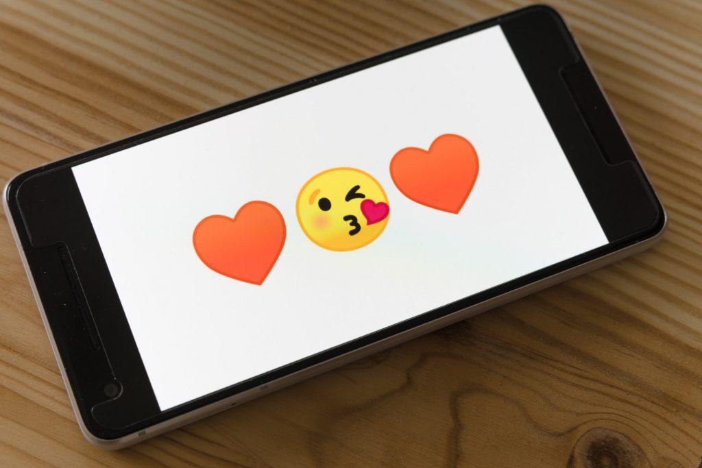 Puhelimen ruudulla kaksi sydän emojita, joiden välissä pusua antava emoji